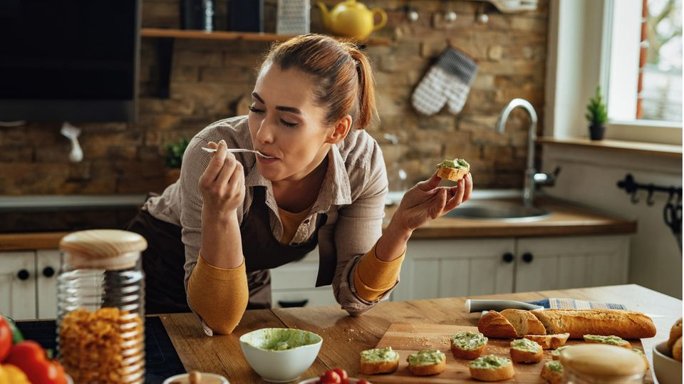 Ernährung: Eine Frau isst genüsslich ein Brot