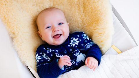 Lammfell im Kinderwagen: Kleiner Junge lacht auf einem Lammfell