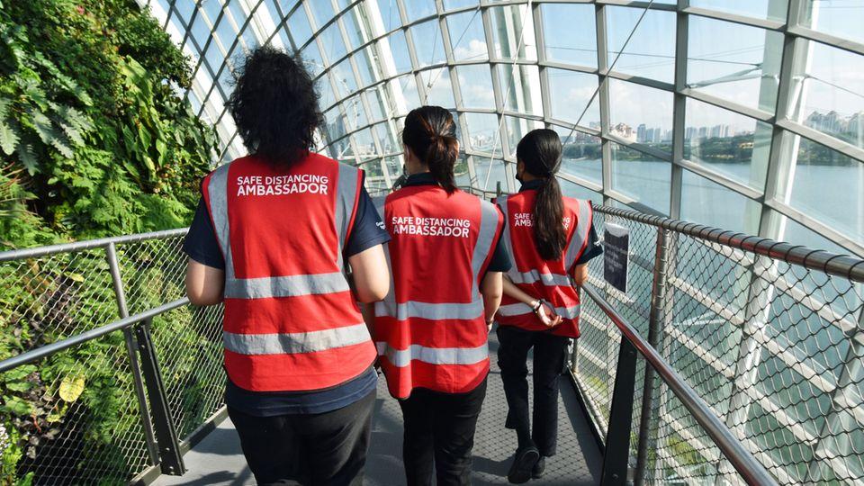 Gehören zum gegenwärtigen Stadtbild: drei von 3000 Safe Distancing Ambassador, die aufpassen, dass sich Menschen an belebten Orten nicht zu nahekommen.