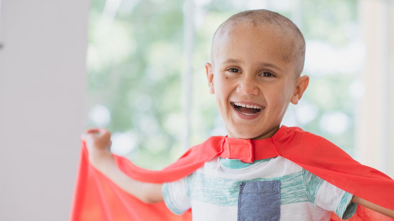 Ein an Krebs erkranktes Kind trägt ein Superman-Cape und lacht