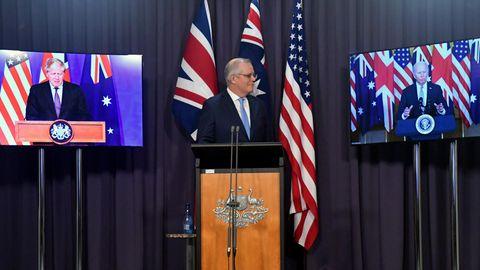 Scott Morrison (M) steht einer Bühne während einer Videoschalte mit Boris Johnson (l) und Joe Biden