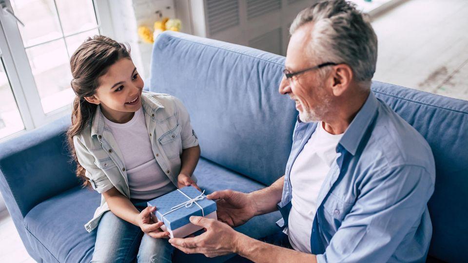 Ein Vater überreicht seiner Tochter ein Geschenk