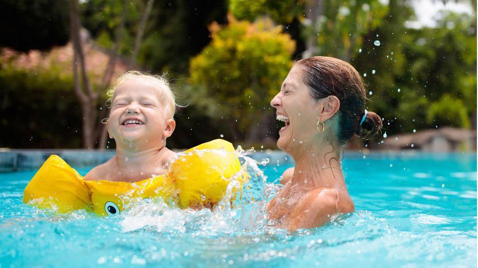Schwimmhilfen für Kinder: Kleiner Junge mit Schwimmflügeln und seiner Mutter im Pool