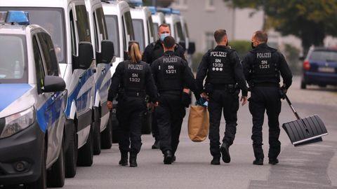 Bereitschaftspolizisten gehen neben ihren Fahrzeugen.