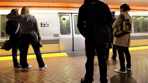 Menschen stehen an einem unterirdischen Bahnsteig