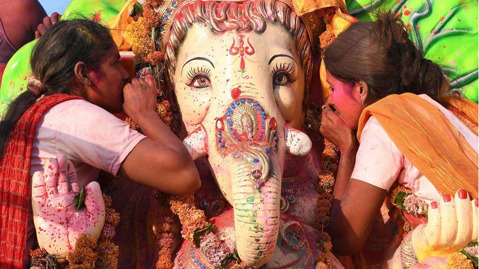 Amritsar, Indien. Zwei Frauen huldigen dem elefantenköpfigen Hindu-Gott Ganesha. Die Figursteht am Rand der Millionenstadt, wo in diesen Tagen das Ganesh-Chaturthi-Festival zu Ehren der Geburt der Haupt-Gottheit der meisten Hindus gefeiert wird. Es ist das wichtigste Fest des Jahres, bei dem es nicht nur Gottesdienste, sondern auch Musik, Tanz und Prozessionen gibt. Das Fest feiern Hindus in der ganzen Welt.