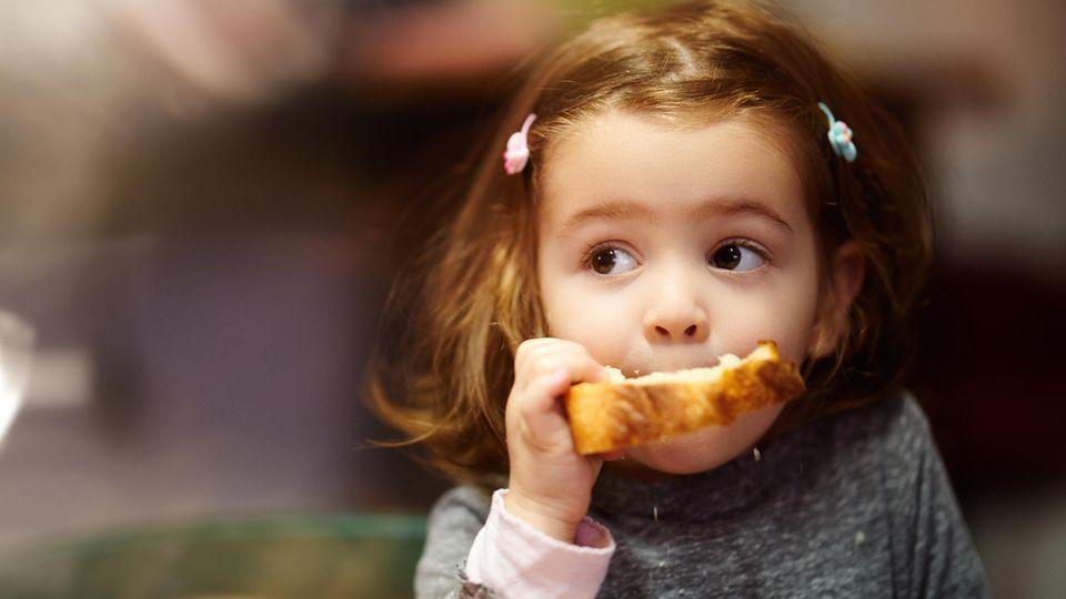 Ein kleines Mädchen beißt in eine Scheibe Toastbrot