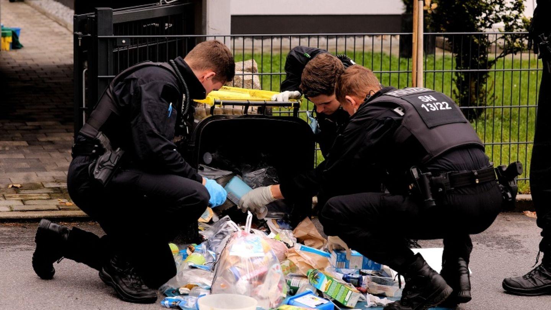 Polizisten durchsuchen in der Umgebung des Tatorts eine Mülltonne