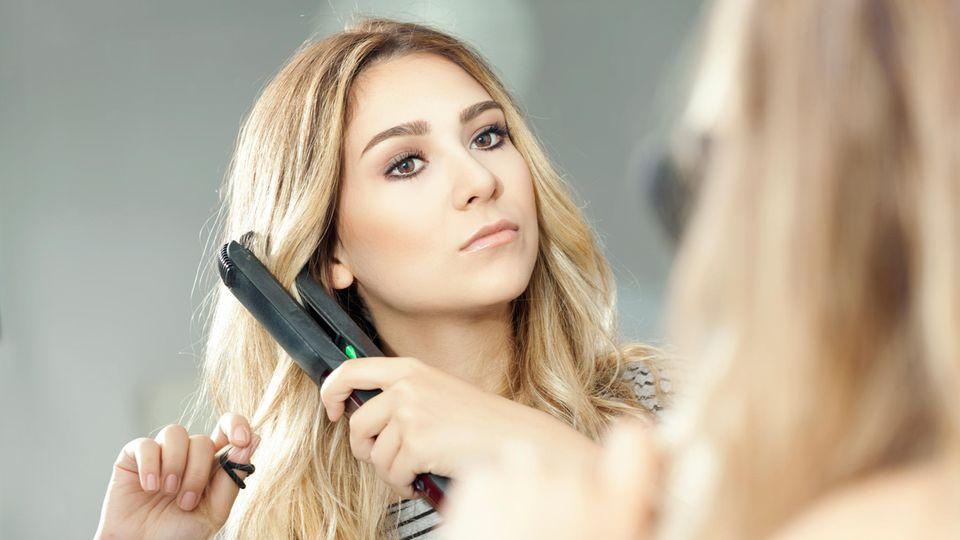 Dyson Corrale: Eine Frau glättet ihre Haare mit einem Glätteisen.