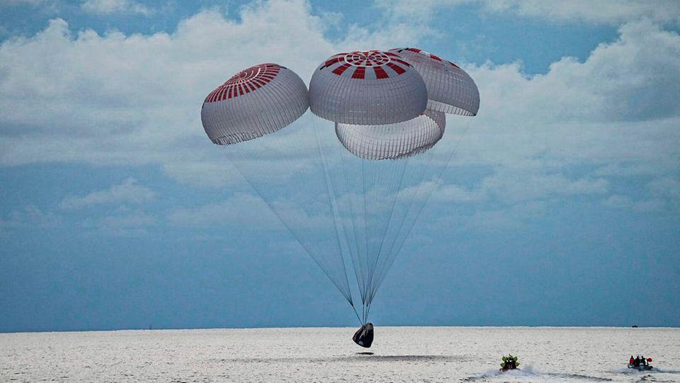 In diesem Bild aus einem SpaceX-Video gleitet eine SpaceX-Kapsel mit vier Personen an Bord vor der Küste Floridas mit Fallschirmen in den Atlantik.
