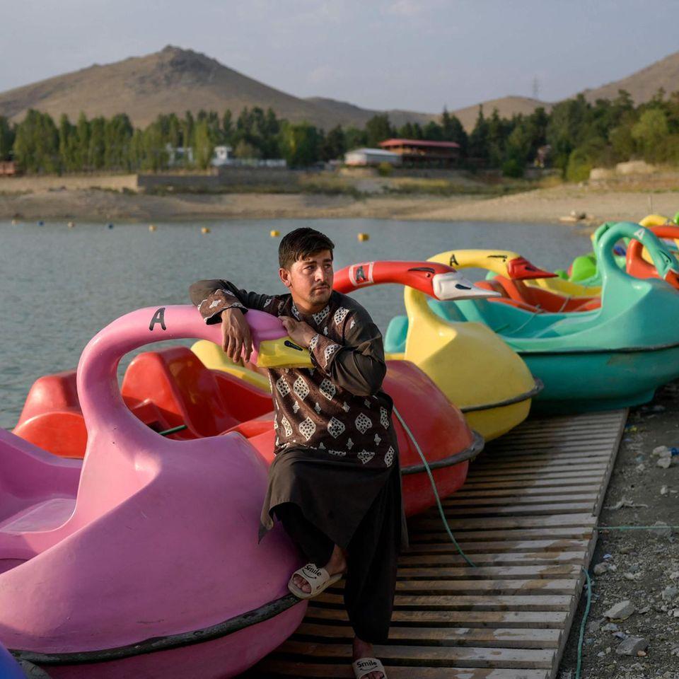 """Kabul, Afghanistan. DasQargha Reservoir liegt am westlichen Rand der afghanischen Hauptstadt und ist ein Naherholungsgebiet. Doch nachdem die Taliban die Macht im Land an sich gerissen haben,scheint niemandem danach zu sein, ein Schwanen-Tretboot auszuleihen. Der """"Schwanenvater"""" wartet jedenfalls vergeblich auf Kundschaft."""