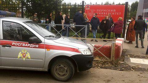 Ein silber-rotes Polizeiauto steht vor einem Metallzaun mit einem roten Schild mit kyrillischer Schrift darauf