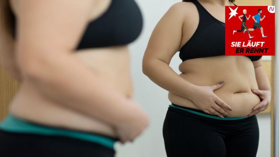 Eine Frau betrachtet ihren Bauch im Spiegel
