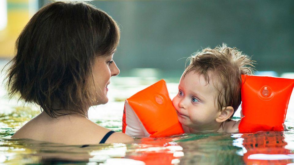 Schwimmhilfen für Kinder: Kleiner Junge mit Schwimmflügeln und seiner Mama in einem Schwimmbecken