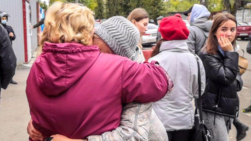 Perm Schießerei Unizwei ältere Frauen liegen sich in den Armen, die Umstehenden sehen geschockt aus