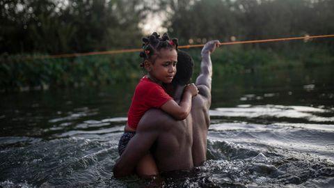 Ein Vater überquert mit seiner Tochter den Rio Grande