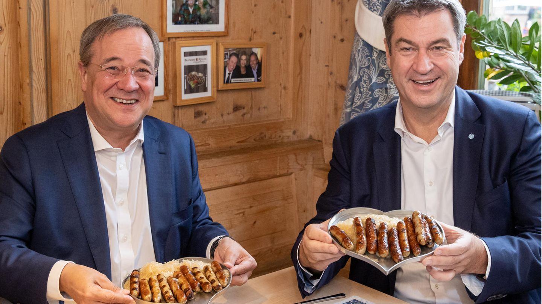 Armin Laschet und Markus Söder am Tisch mit einem Teller Nürnberger Würstchen