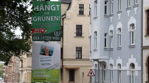 """Ein Wahlplakat der Splitterpartei """"III. Weg"""" hängt oberhalb eines Plakates der Grünen."""