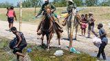 Berittene Beamte der US-Zoll- und Grenzschutzbehörde versuchen, haitianische Migranten aufzuhalten