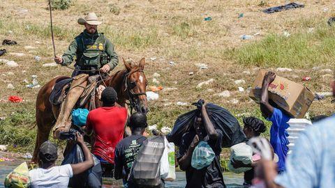 Ein berittener Beamter der US-Zoll- und Grenzschutzbehörde versucht, haitianische Migranten aufzuhalten
