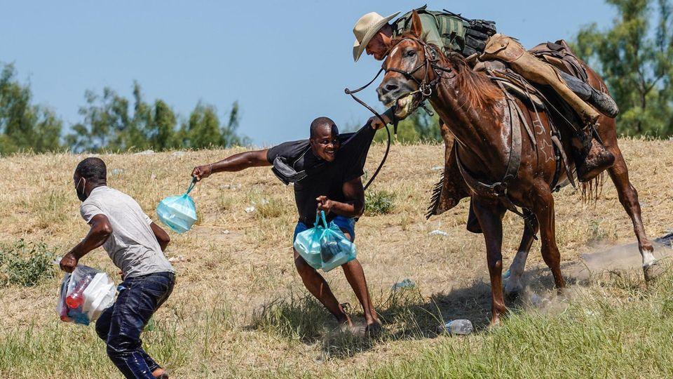 Ein berittener Beamter der US-Zoll- und Grenzschutzbehörde versucht, einen haitianischen Migranten aufzuhalten