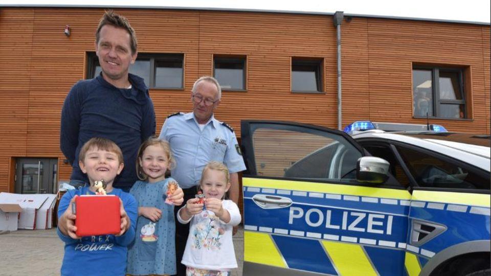 """Polizeihauptkommissar Rainer Stach übergab die rote Erzählbox und drei Figuren an den stellvertretenden Leiter der Kita """"Wundertüte"""", Marcel Rau, und drei Kinder"""