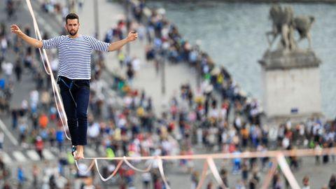 Ein junger weißer Mann mit Vollbart läuft in blau-weißem Ringelshirt auf einem Seil in 70 Metern Höhe