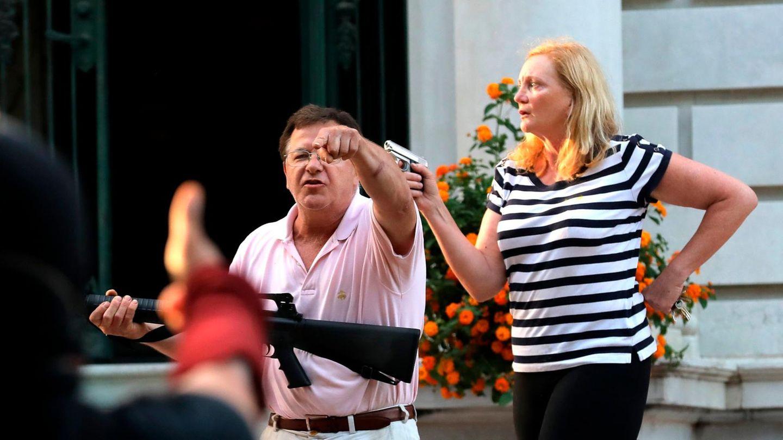 Ein weißer Mann mit weißer Hose und rosa Poloshirt hält ein Sturmgewehr in seinen Händen, eine weiße Frau hält eine Pistole hoch
