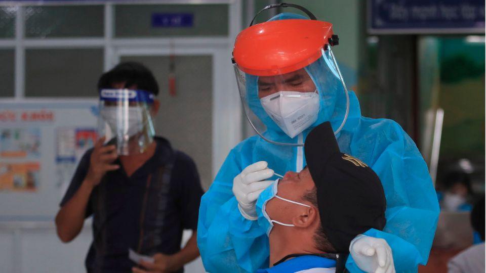 Ein Mitarbeiter im vietnamesischen Gesundheitswesen entnimmt einem Mann einen Abstrich