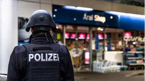 Ein Polizist sichert am frühen Morgen eine Tankstelle