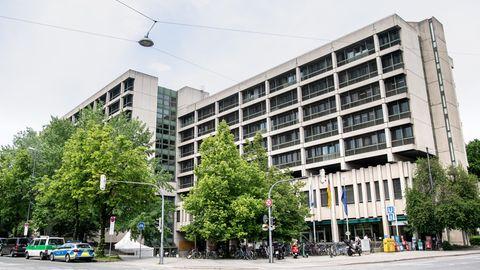 Hinter einer mehrspurigen Kreuzung steht ein mehrstöckiges betongraues Gebäude
