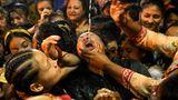 Kathmandu, Nepal.Gläubige trinken Wein aus einer Statue von Shwet Bhairav (Gott des Schutzes) während des Indra Jatra-Festes. Das achttägige Festival wird im September gefeiert und ist das größte religiöse Straßenfest inKathmandu.