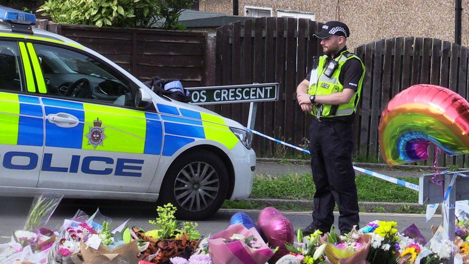 Ein uniformierter Polizist steht an einer Absperrung, an der Menschen Blumen für die vier Ermordeten niederlegen