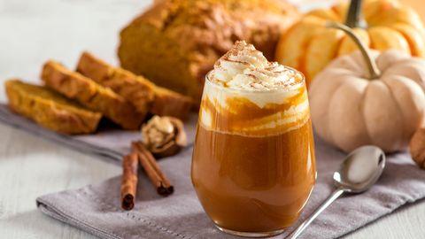Ein Pumpkin Spice Latte neben Kürbissen und Kuchen