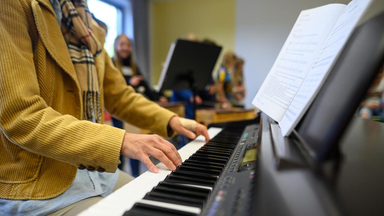 Eine Frau spielt auf einem Klavier, vor ihr steht ein aufgeschlagenes Notenheft