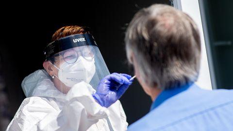 Eine weiße Frau in weißer Schutzkleidung, mit Brille und Gesichtsschirm steckt einem grauhaarigen Mann einen Wattestab