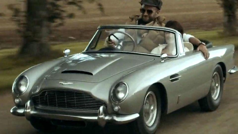 """Das silbergraue Auto aus """"James Bond: Goldfinger"""" im Miniformat fährt über eine Landstraße"""