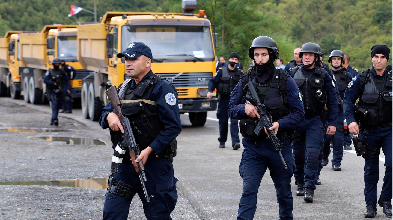 Bewaffnete Polizisten in Einsatzkleidung patrouillieren auf einer Straße, im Hintergrund sind Lastwägen zu sehen.