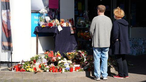 Von hinten sind ein Mann und eine Frau zu sehen, die vor Kerzen und Blumen an einer Tankstelle innehalten