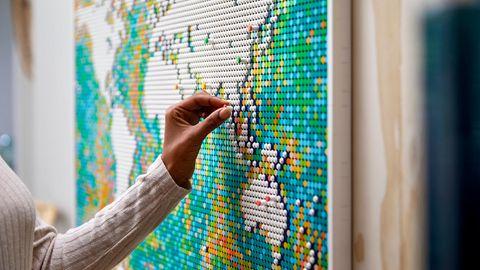 Lego Art World Map zum Hammerpreis: Frau steckt einen Pin an die Lego-Weltkarte