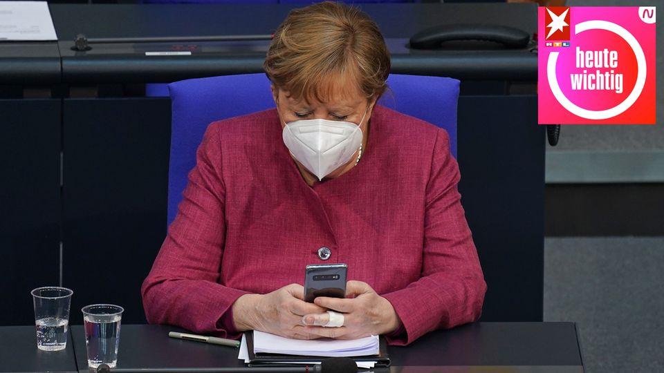 Angela Merkel schaut im Bundestag auf ihr Smartphone