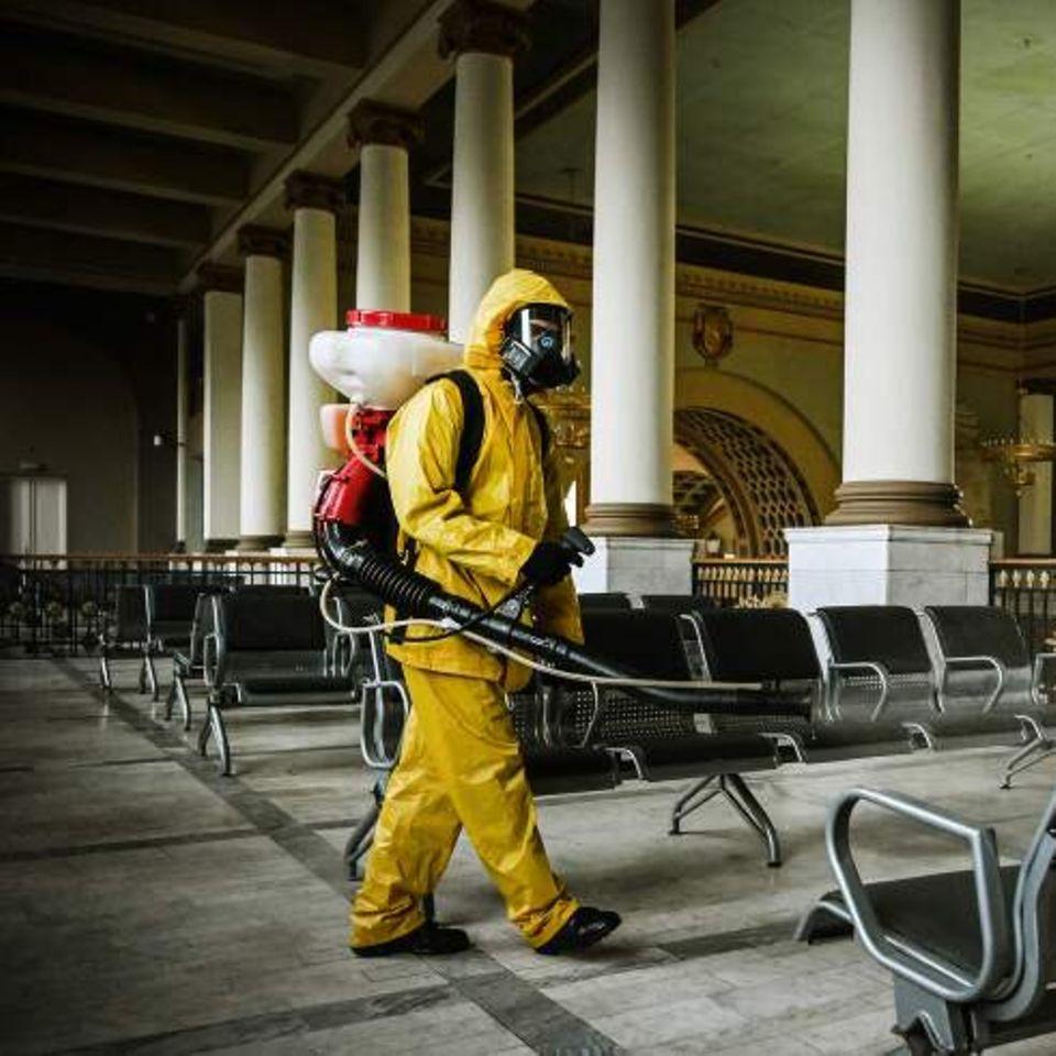 Ein Mitarbeiter des russischen Katastrophenschutzes in Schutzkleidung desinfiziert den Kiewer Bahnhof