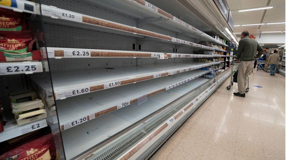 Großbritannien, Manchester: Eine Person steht vor leeren Regalen in einem Supermarkt