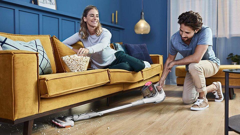 Philips SpeedPro Akku-Staubsauger: Mann saugt Krümel unter einem Sofa auf