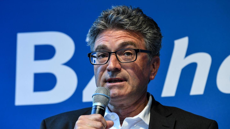 Ein weißer Mann mit schwarzer Brille und grauem, gelocktem Haar spricht in das Mikro in seiner rechten Hand