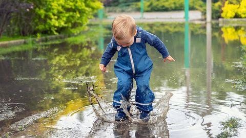Ein Kind spielt mit Matschhose in einer großen Pfütze