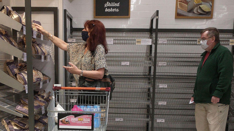 Eine Frau steht vor einem leeren Regal in einem Supermarkt in London
