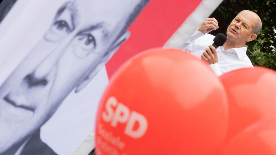 Olaf Scholz, sein Plakat und SPD-Ballons