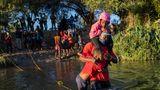 Ein haitianischer Vater trägt seine Kinder über den Rio Grande nach Del Rio, Texas