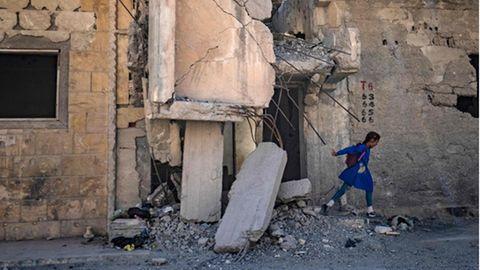 Ein kleines Mädchen geht zur Schule, vorbei an zerstörten Gebäuden in Ar-Raqqa, Syrien